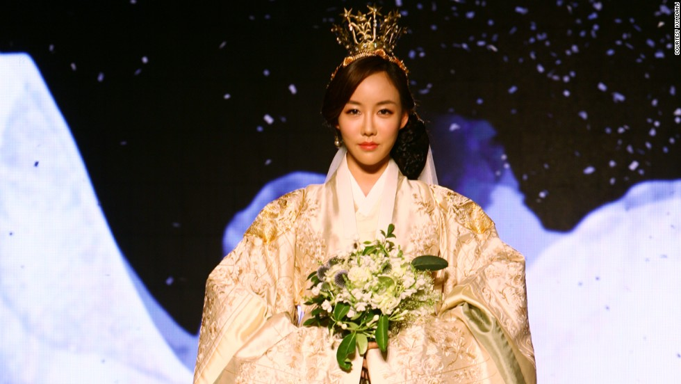 "Yi Seong Hye, <a href=""http://travel.cnn.com/seoul/life/interview-miss-korea-2011-korean-fashion-big-dreams-and-plastic-surgery-095759"" target=""_blank"">Miss Korea in 2011</a>, models Kumdanje's 2013 bridal line. The white hanbok evokes the 1870s, when Western influences came to Korean clothing for the first time and brides modified their hanbok in the Western bridal style, wearing them with veils and lace undertones."