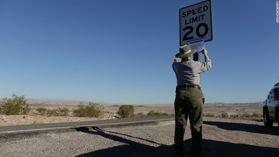 "Park maintenance worker Donna Curry tapes up a sign on October 1 notifying visitors the picnic facility in Lake Mead National Recreation Area near Boulder City, Nevada, is closed. A Nevada couple told CNN affiliate <a href=""http://www.ktnv.com/news/local/226557661.html"" target=""_blank"">KTNV-TV</a> they were kicked out of their cabin, which is on federal land."
