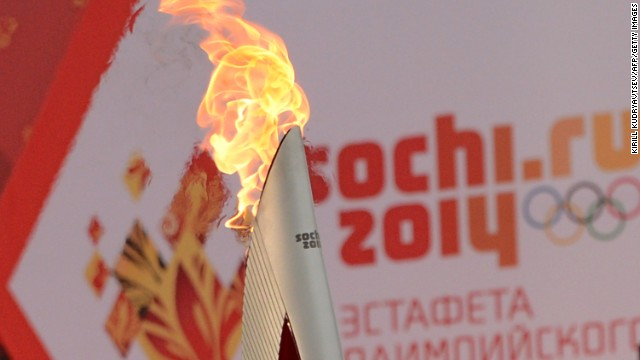 One of the Olympic torches rises in front of a poster with the Sochi 2014 Winter Olympic logo just outside the Red Square in Moscow, on October 7, 2013, during a ceremony to kick off the Sochi 2014 Winter Olympic torch relay across Russia. AFP PHOTO / KIRILL KUDRYAVTSEV (Photo credit should read KIRILL KUDRYAVTSEV/AFP/Getty Images)