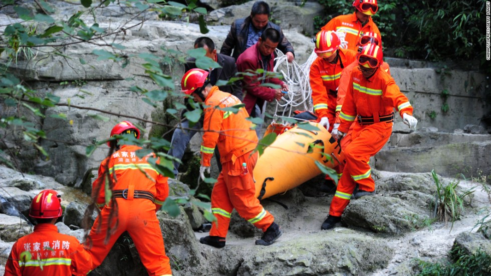 Rescuers carry Kovats' body down the mountainside on October 9. Nearly 200 firefighters and police officers were involved in the search operation, according to Xinhua.