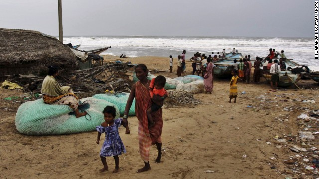 An Indian woman leaves the coast with her children as other villagers look at the Bay of Bengal, India, on Friday.