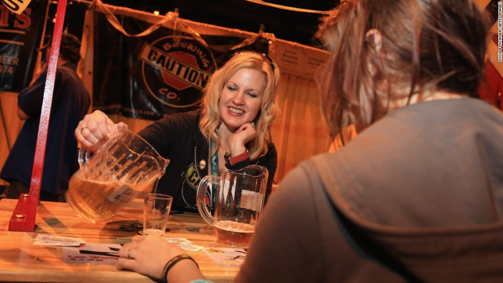 Betty Wang of Caution Brewery in Denver, Colorado pours beer for a festival goer.