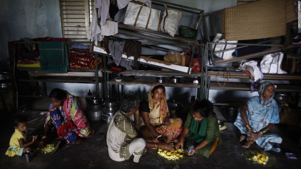 Evacuated villagers eat in a temporary cyclone shelter in the town of Chatrapur, India, on October 12.