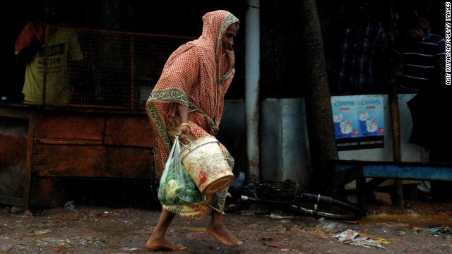 An elderly Indian woman carries daily essentials as she walk in a heavy cyclonic wind in Gopalpur, about 190 kilometers south of eastern city Bhubaneswar on October 12, 2013.   Nearly half a million people have been evacuated from India's impoverished east coast ahead of a massive cyclone expected to make landfall on October 12 evening, disaster officials said.  AFP PHOTO/ASIT KUMAR        (Photo credit should read ASIT KUMAR/AFP/Getty Images)