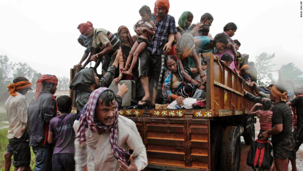 Evacuated villagers climb down from a truck at a relief camp near Berhampur on October 12