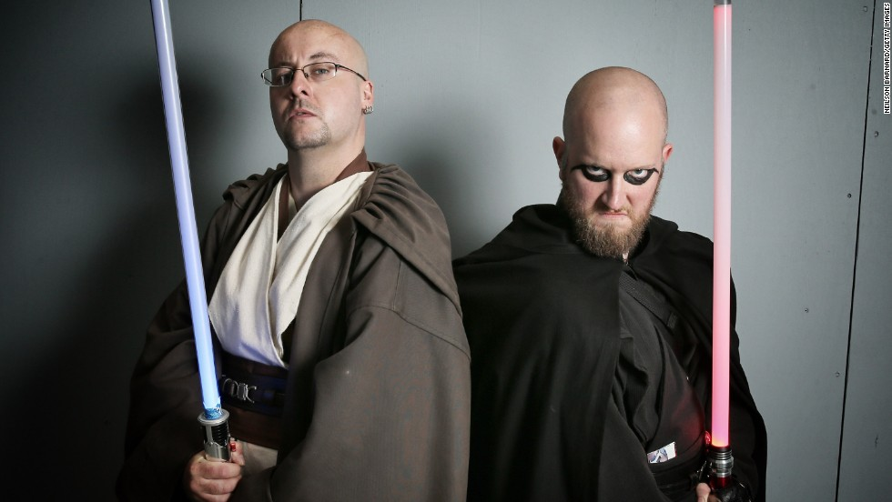 These fans pose as Jedi's of the light and dark side of the force.