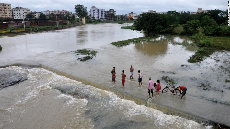 People stand in the overflowing waters of the Swarnrekha River in Ghaghra, India, on October 14.