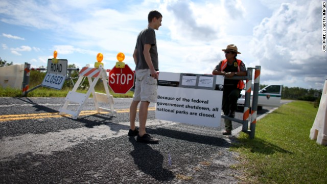 Mirta Maltes a U.S. Park Ranger law enforcement officer speaks with Christoph Zuercher, a tourist from Switzerland, at a road closed sign leading to the Everglades National Park after he discovered the park was closed on October 7, in Miami, Florida.