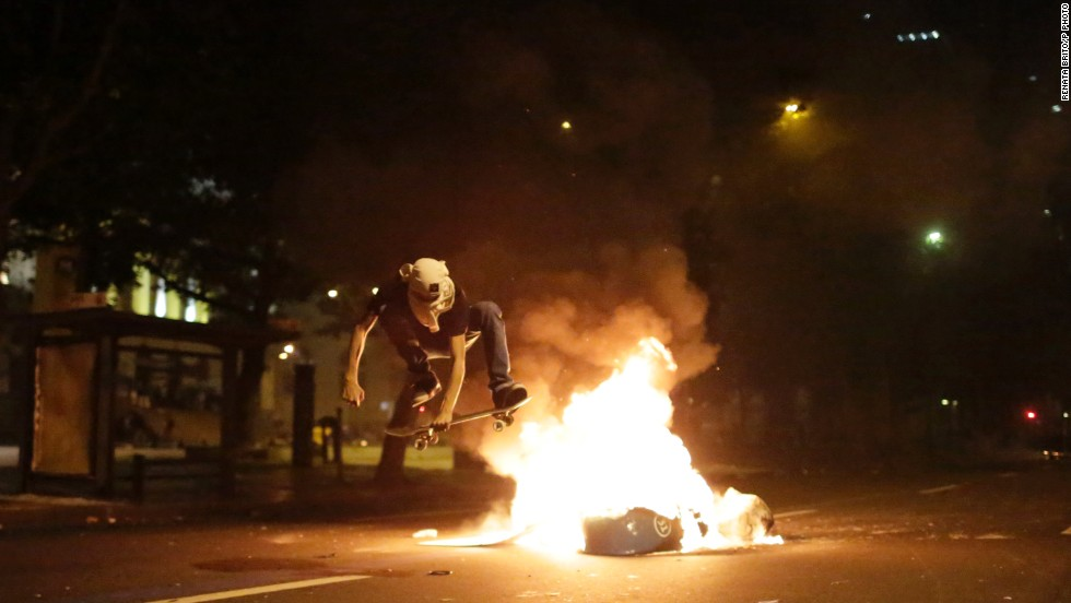"OCTOBER 16 - RIO DE JANEIRO, BRAZIL: A Black Bloc anarchist jumps a burning barricade, after a peaceful march of striking teachers ended in clashes between anarchist protesters and the police. People took to streets on Brazilian Teachers Day,  demanding <a href=""http://www.cnn.com/2013/10/08/world/gallery/brazil-teacher-protests/index.html"">better pay and affordable housing for educators</a>."
