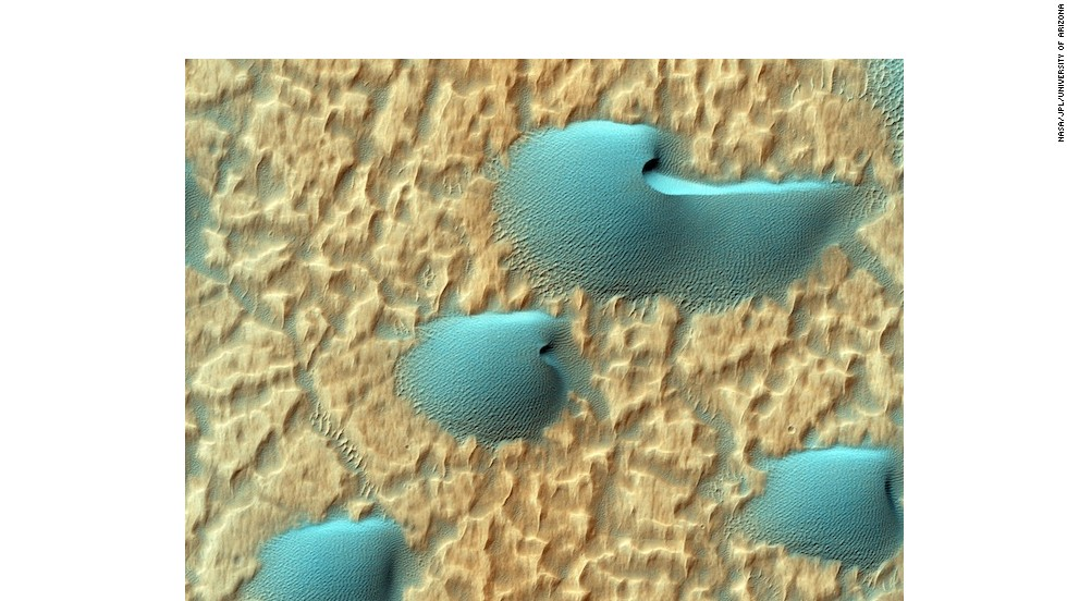 "What's up with the strange colors of these dunes? Mars isn't really blue and gold, it's just that this picture was taken in infrared wavelengths to better show the composition of the sand here. But these dunes, known as ""<a href=""http://hirise.lpl.arizona.edu/ESP_033272_1400"" target=""_blank"">barchans</a>,"" would look striking in any light: they often form cool horns or notches on their steep leeward sides."