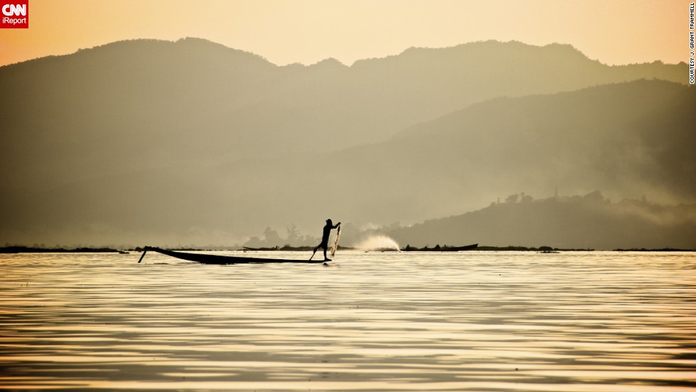 "A ""leg spinner"" paddles across Inle Lake in Myanmar. The unique style of paddling involves using one leg to power the boat while balancing on the canoe's edge with the other, freeing up the hands for fishing. ""It is very interesting and beautiful to watch as it takes incredible balance and coordination,"" <a href=""http://ireport.cnn.com/docs/DOC-840861"">J. Grant Trammell</a> said."