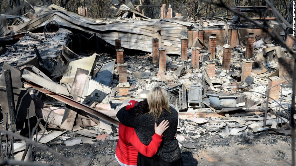 Victims look over the remains of their home on Friday, October 18, after a devastating bush fire passed through Winmalee in the Blue Mountains.