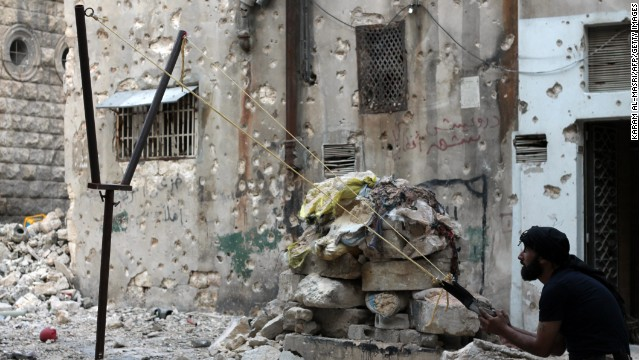 A Syrian opposition fighter aims fire with a catapult towards regime forces in Aleppo on Thursday, October 17. More than 100,000 people have reportedly been killed in Syria since a popular uprising spiraled into a civil war in 2011. Click through to view the most compelling images taken since the start of the conflict.