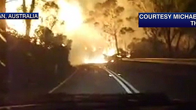 Firefighter drives through huge flames