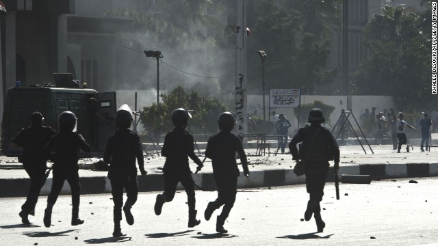 Riot police run toward students outside the al-Azhar University in Cairo on Sunday during a pro-Morsy demonstration.