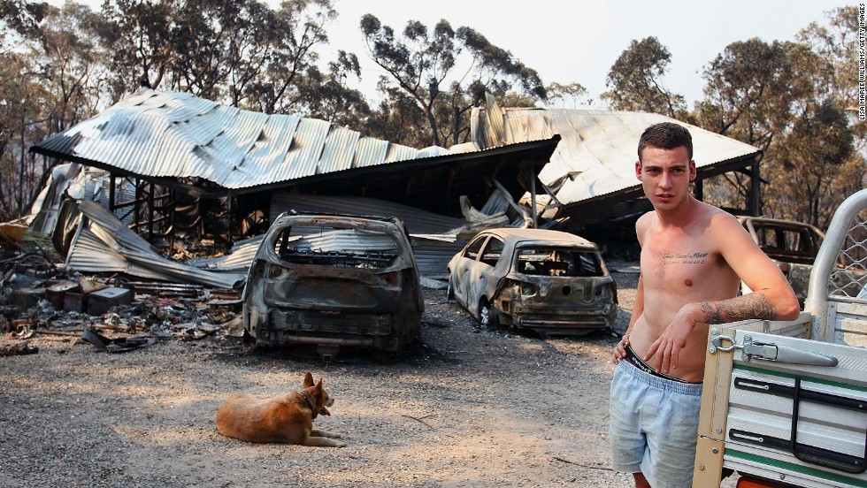 A man in Yellow Rock, Australia, stands in front of a building on Monday, October 21, that was destroyed by the bush fires scorching the country's eastern state of New South Wales.
