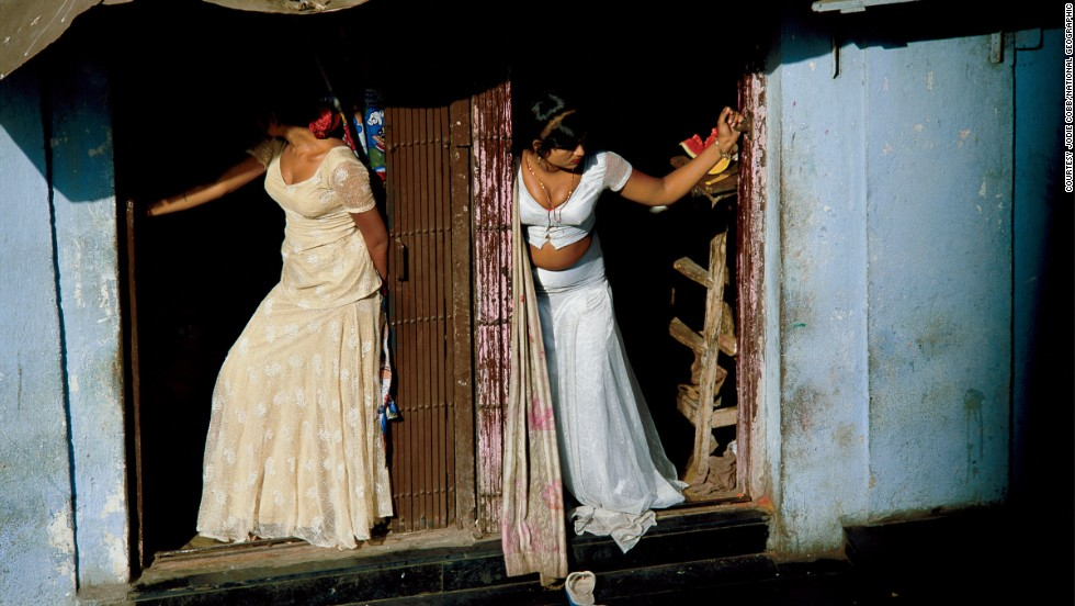 Jodi Cobb joined National Geographic as one of the magazine's first female staff photographers, in 1977. In this image she captures prostitutes, who are known as cage girls and are often sex slaves, displaying themselves on a Mumbai street.