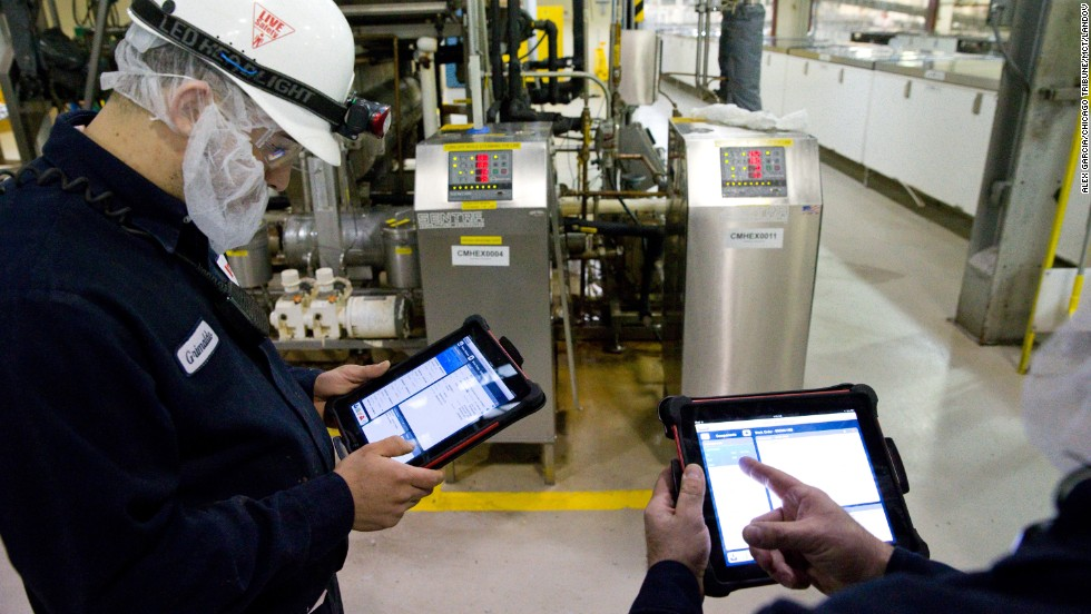 Technician Grimaldo Romero, left, uses his iPad to help maintain machinery at the World's Finest Chocolate plant in Chicago, Illinois, on March 21, 2013.