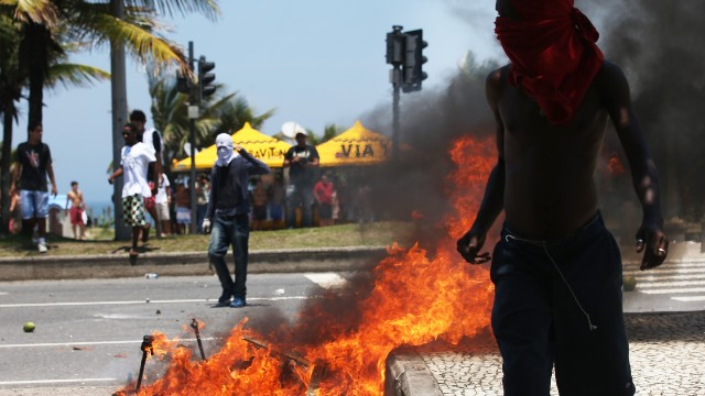 A masked protester passes a fire during demonstrations over the sale.