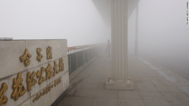 A woman stands on a bridge under heavy smog in Harbin, northeast China's Heilongjiang province, on October 21, 2013. Choking clouds of pollution blanketed Harbin, which is famed for its annual ice festival, reports said, cutting visibility to 10 metres (33 feet) and underscoring the nation's environmental challenges. CHINA OUT AFP PHOTO (Photo credit should read STR/AFP/Getty Images)