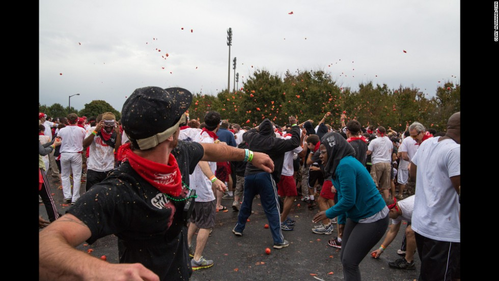 Hundreds of people throw and dodge rotten tomatoes during the Tomato Royale, part of the Great Bull Run event on October 19.
