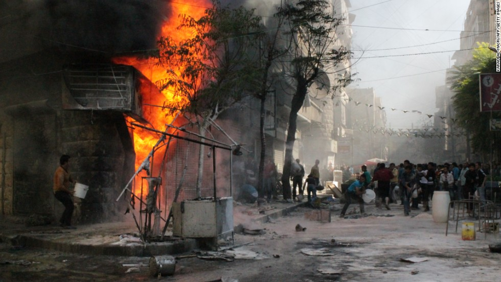 People use buckets as they try to extinguish a fire that ignited at a  fuel station in Aleppo, Syria, on Sunday, October 20.