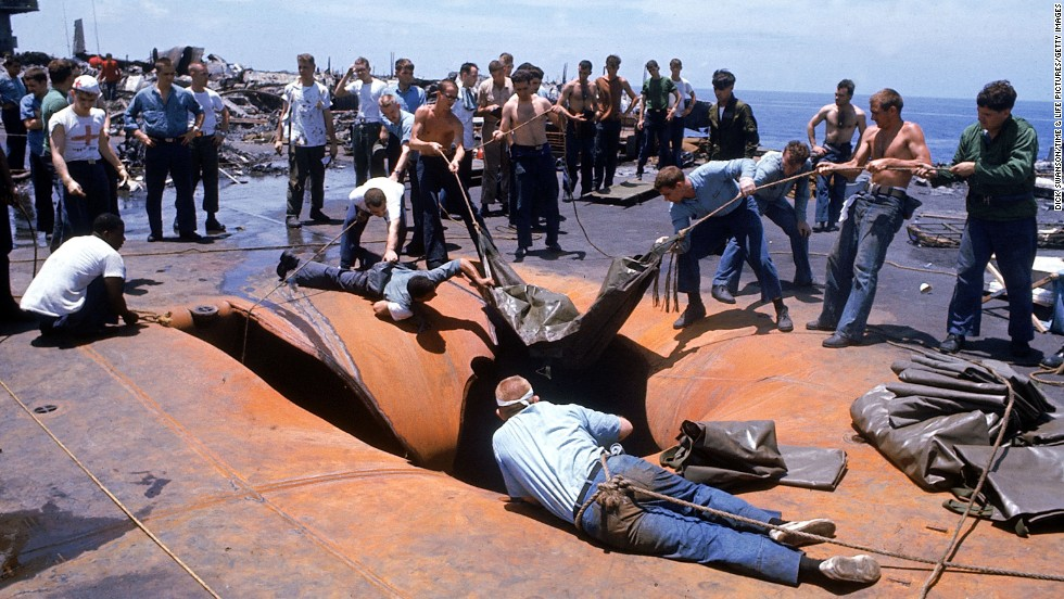Crew members look through a hole in the deck of the USS Forrestal in search of survivors after the explosion in July 1967.