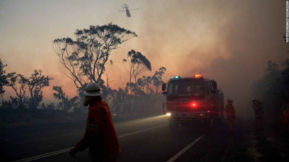 New South Wales Rural Fire Service crew members fight a fire near Mount Wilson in the Blue Mountains of Australia on Thursday, October 24. Wildfires threatened the western suburbs of Sydney on Wednesday as high winds and temperatures created at least a dozen new fires that were blazing across a 1,000-mile stretch of New South Wales.