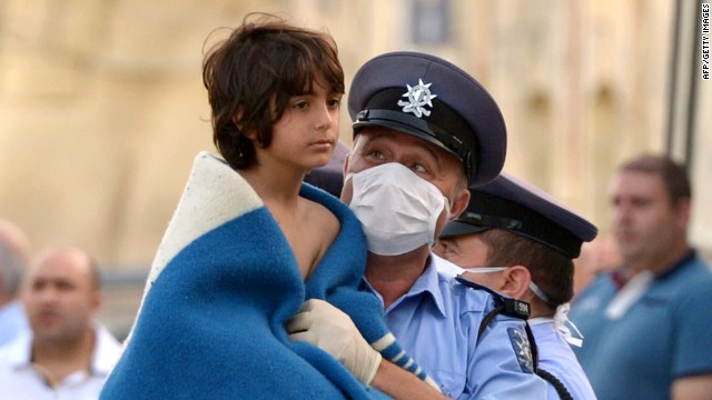 A Maltese policeman carries a child rescued by the Armed forces of Malta at Hay Wharf in Valletta on October 12, 2013.