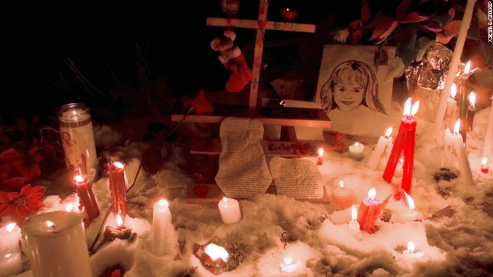 "Candles surround a portrait of JonBenet outside her Boulder home after a candlelight vigil on the one-year anniversary of her murder on December 26, 1997. A year after the murder, Boulder police indicated John and Patsy Ramsey were under ""an umbrella of suspicion,"" and would  be questioned again."