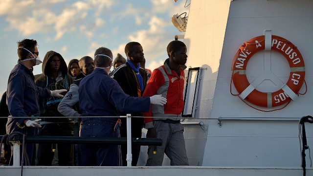 Some 100 migrants stand on the Guardia Costiera boat after being rescued off the shores of the island of Lampedusa on October 25, 2013. Two boats with other 219 migrants were picked up by Italian Navy ships deployed in Italy's new Mare Nostrum search-and-rescue operation, launched after more than 400 migrants drowned in two disasters earlier this month. Nearly 700 refugees were rescued off Sicily in several operations as European leaders grapple with the issue of illegal immigration at a European Union summit. AFP PHOTO / FILIPPO MONTEFORTEFILIPPO MONTEFORTE/AFP/Getty Images