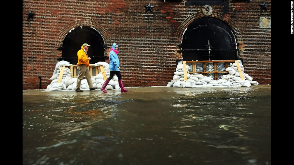 People walk past sandbags on a flooded street in the Red Hook section of Brooklyn, New York, as Hurricane Sandy moves closer to the area on October 29, 2012.