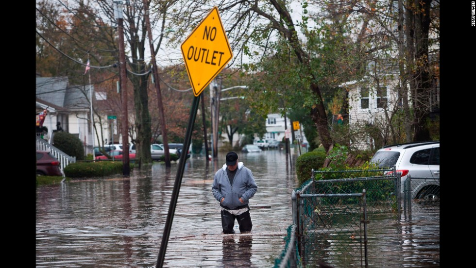 A man walks through a flooded street on October 30, 2012, in Little Ferry, New Jersey.