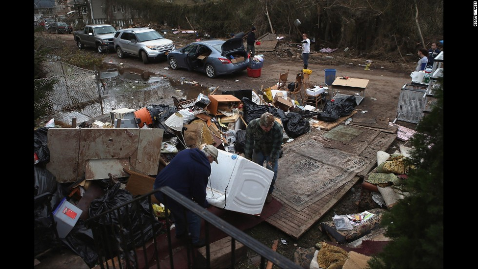 Members of the Hague family try to salvage a washing machine from their flood-damaged home on November 1, 2012, in the Ocean Breeze area of Staten Island, New York.