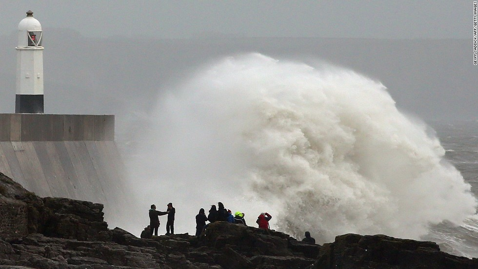 People stand on the rocks as large waves break against the harbor in Porthcawl, Wales, on Sunday.