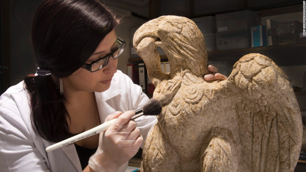 Museum of London Archaeology conservator Luisa Duarte dusts a Roman sculpture of an eagle clutching a serpent, dating from the first or second century. It was dug up at a site in the City of London, the UK capital's financial center, which is known once to have been home to a Roman cemetery. The statue is 26 inches tall and made of limestone. It will be on display at the Museum of London for the next six months.