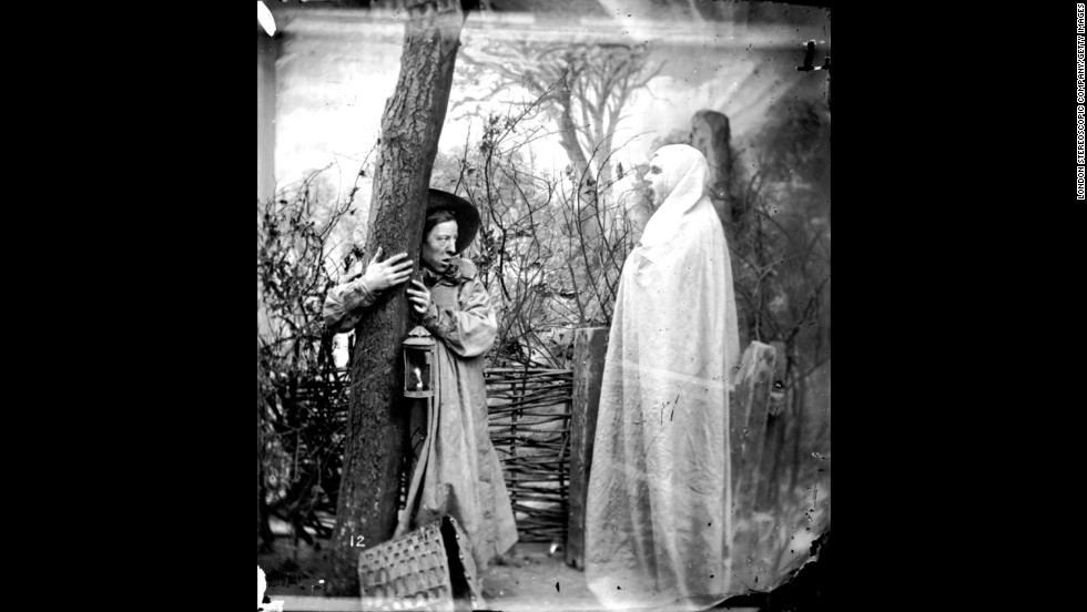A man clings to a tree in the face of an apparition in a forest.