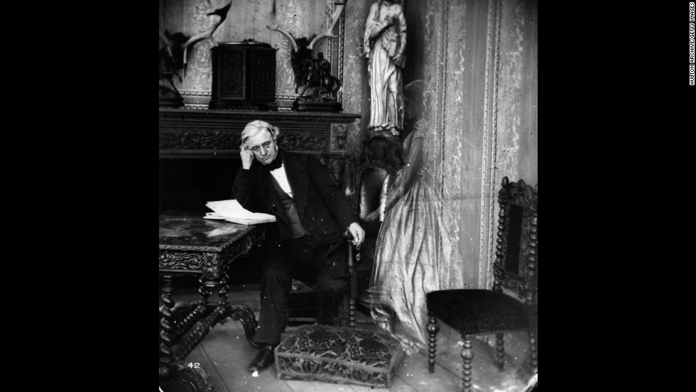 A ghostly figure visits a man reading in his sitting room.