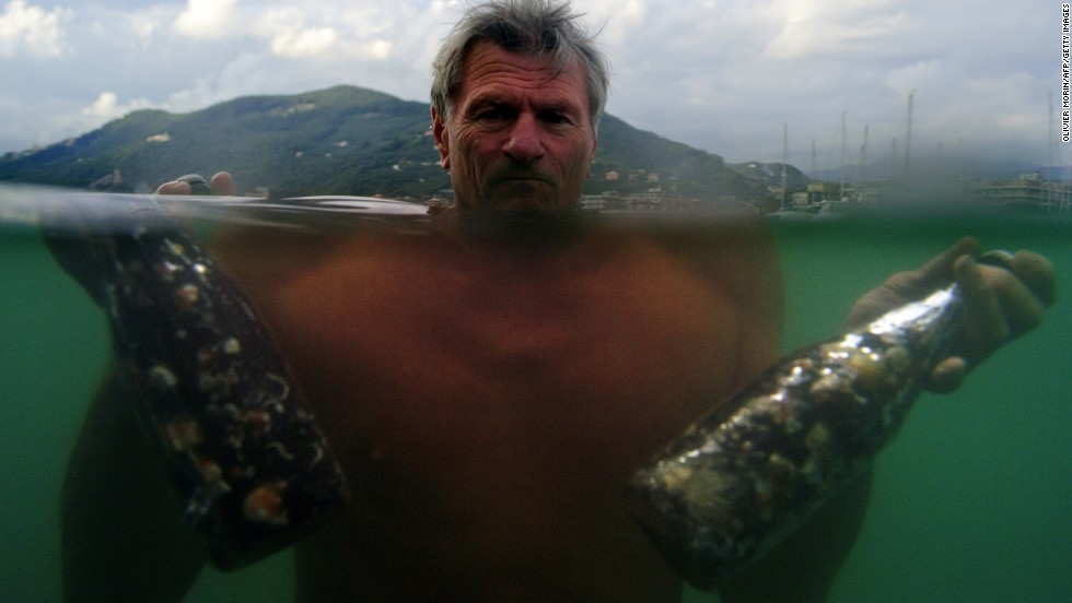 Pierluigi Lugano, an Abissi winemaker, poses in the sea with two bottles of wine which he brought to the surface in Chiavari. Lugano is experimenting by storing his wine three to four years in the sea at a depth of about 197 feet and some two miles offshore, where the water temperature remains constant.