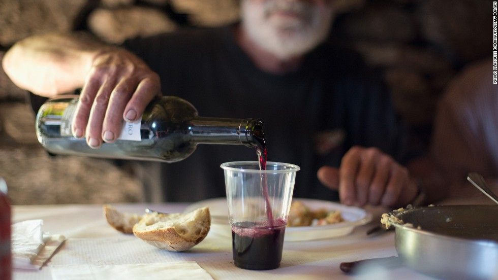 Antonio Perez pours a glass of wine during lunch at a Cruceiro Reixo's plot in the region of Ribeira Sacra, Spain.
