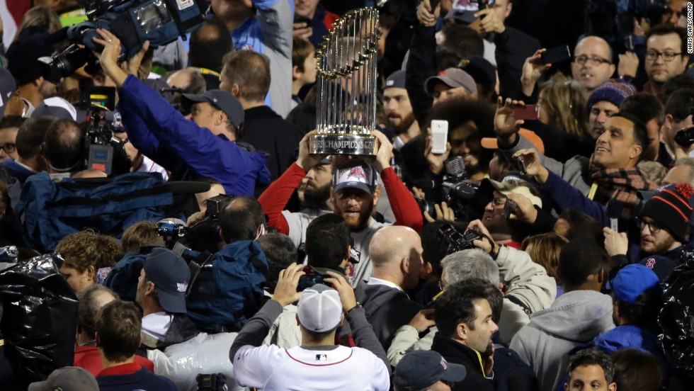 Boston Red Sox players hold up the championship trophy after Game 6 of baseball's World Series against the St. Louis Cardinals on Wednesday, October 30, in Boston. The Red Sox defeated the Cardinals 6-1.