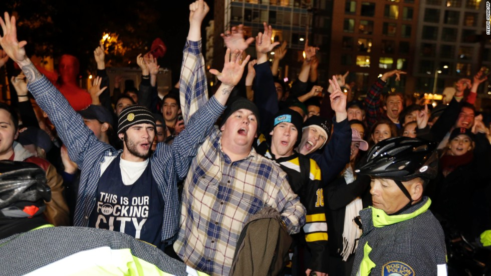 Fans are ushered along a street by law enforcement officials.