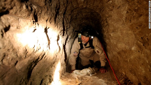 A Homeland Security Special Agent crawls through a drug tunnel at a warehouse near the U.S.-Mexico border in 2010.