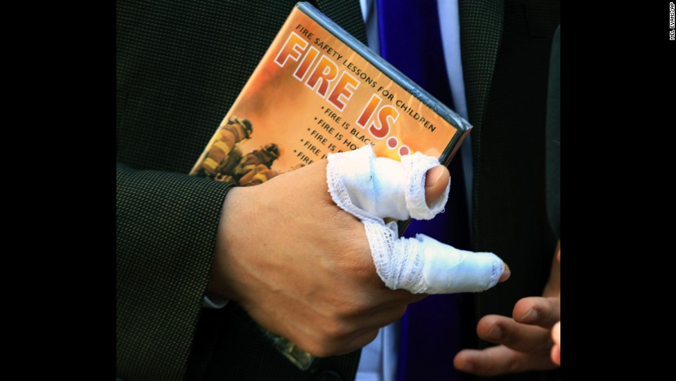 Booker's bandaged right hand holds a children's fire safety video that was given to him by a well-wisher in April 2012. Booker made national headlines then for rescuing a next-door neighbor from a fire.