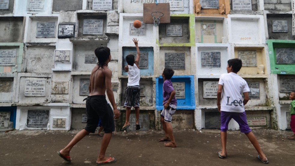 "OCTOBER 31 - MANILA, PHILIPPINES: Youngsters play basketball at a cemetery, marking one of the most important holidays for the largest Catholic nation in Asia, <a href=""http://edition.cnn.com/SPECIALS/cnn-celebrates"">All Saints' Day</a>. Filipinos traditionally visit cemeteries to hold vigils and large family reunions, but the atmosphere is far from sad, as the usually silent graveyards turn into parties with food and music."