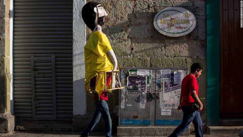 """A paper mache costumed character walks through the streets of Oaxaca. """"At first, children a bit scared of the costumes and skull painting because they don't know what it means,"""" says Valentin Concha-Nunez, museum educator for El Museo del Barrio in New York. """"But when I tell them to touch their craniums they realize that skulls are a part of them and then they embrace that aspect of it."""""""