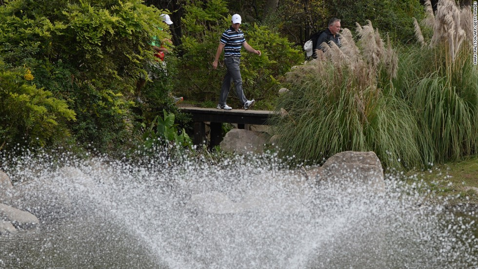 McIlroy walks over the bridge next to the spectacular fountain on the eighth hole at Sheshan International.