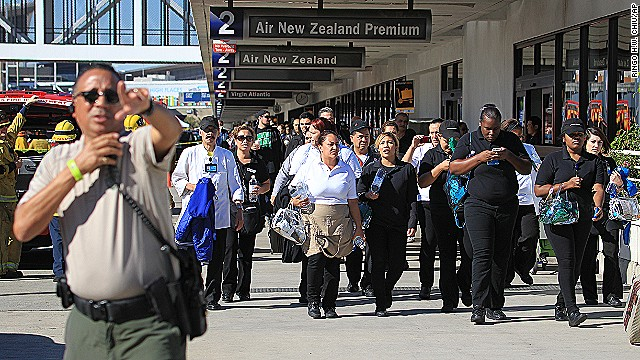 Passengers are directed outside Terminal 2 at Los Angeles International Airport on Friday Nov. 1, 2013, after shots were fired prompting authorities to evacuate a terminal and stop flights headed for the city from taking off from other airports. (AP Photo/Ringo H.W. Chiu)