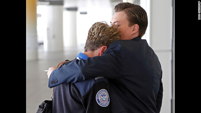 Transportation Security Administration employees hug outside Terminal 1 at Los Angeles International Airport on Friday, Nov. 1, 2013. A gunman armed with a semi-automatic rifle opened fire at Los Angeles International Airport on Friday, killing a Transportation Security Administration employee and wounding two other people. Flights were disrupted nationwide. (AP Photo/Reed Saxon)