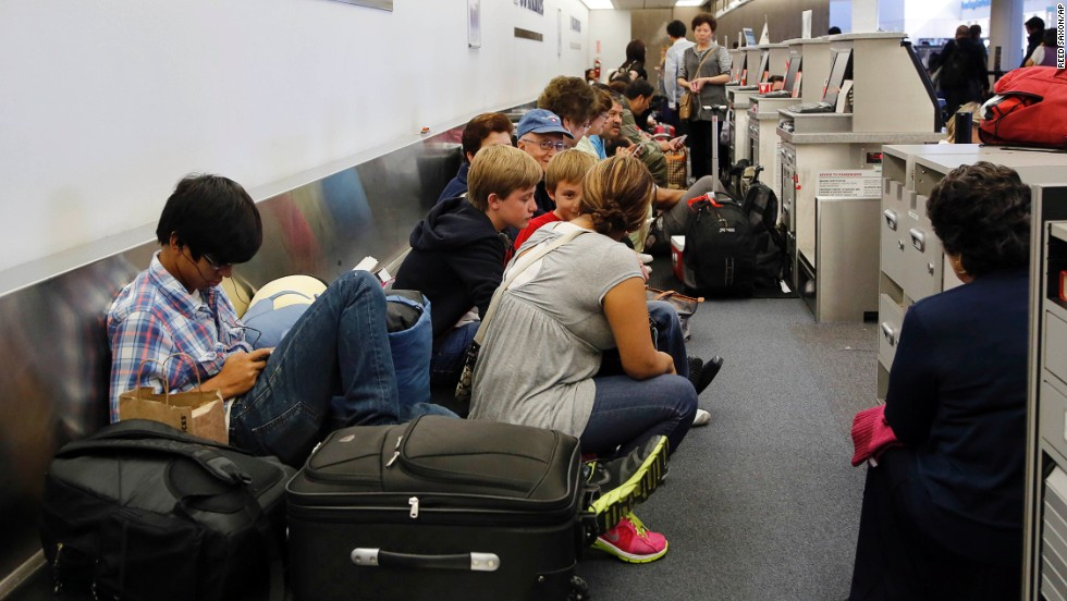 Passengers sit on a luggage conveyor belt behind check-in kiosks in Terminal 1.